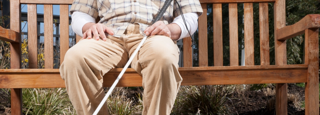 man with a walking stick sitting on a bench