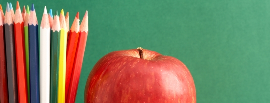 pencil crayons and a red apple