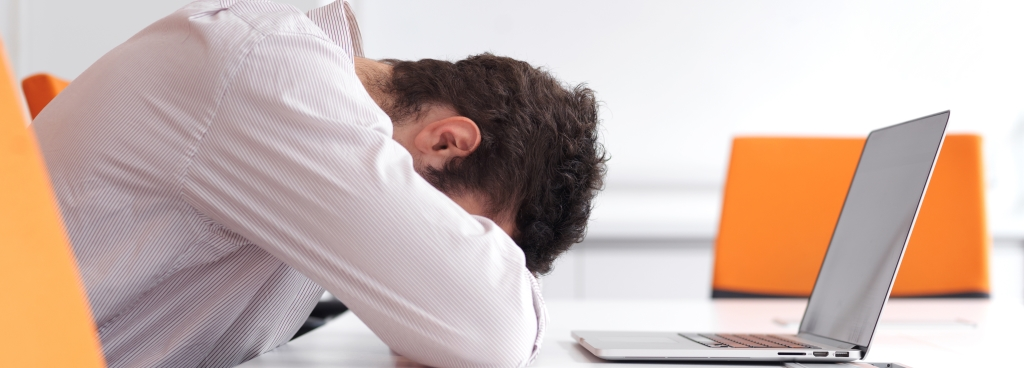 man laying head on table in front of laptop